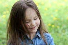 Girl with long hair among dandelion field Stock Photography