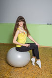 Girl with long hair does exercises in the gym. The beautiful girl sits on a big ball Stock Image