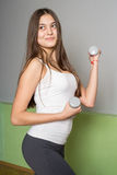 Girl with long hair doing exercises with dumbbells. Portrait of a girl in class in fitness Stock Images