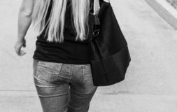 A girl with long hair down to her waist. With a bag on his shoulder. Body part. stock image