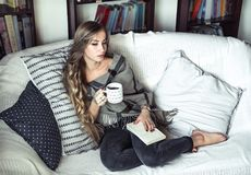 Girl reading a book on the couch stock photos