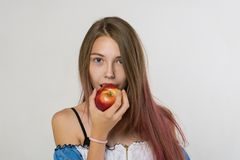 Girl with long hair is eating an Apple over gray background stock photos