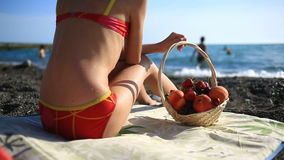 Girl with long hair eating fruit and berries on a crowded sea beach on a background of waves stock footage