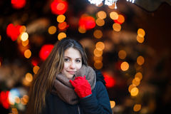 Girl with long hair on European Christmas Market. Young woman Enjoying Winter Holiday Season. Blurred Christmas Lights on backgrou Stock Photo