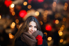 Girl with long hair on European Christmas Market. Young woman Enjoying Winter Holiday Season. Blurred Christmas Lights on backgrou Stock Images