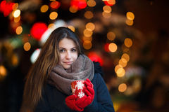 Girl with long hair on European Christmas Market. Young woman Enjoying Winter Holiday Season. Blurred Christmas Lights on backgrou Royalty Free Stock Photo