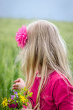 Girl with long hair and flowers. Girl with long blond hair back view and colorful flowers in hand Royalty Free Stock Image