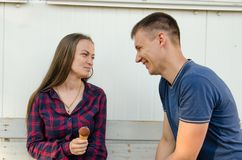 Girl with long hair and freckles and checkered shirt with ice cream in her hand looks at smiling guy in a blue T-shirt stock photos