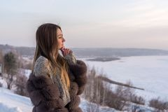 Girl with long hair in a fur coat against the background of a winter valley Royalty Free Stock Photos