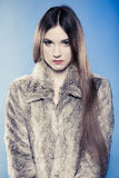 Girl with long hair in fur coat on blue. Royalty Free Stock Photography