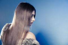 Girl with long hair in fur coat on blue. Royalty Free Stock Photos