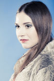 Girl with long hair in fur coat on blue. Royalty Free Stock Photo