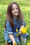 Girl with long hair gathering dandelions in spring Royalty Free Stock Photography