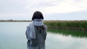 Girl with long hair and a gray sweater with a scarf