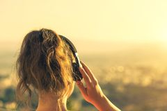 Girl with a long hair in the headphones on the chair on the balcony listening to music on the sunset background royalty free stock photo
