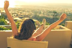 Girl with a long hair in the headphones on the chair on the balcony listening to music on the sunset background stock image