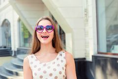 Girl with long hair heart-shaped sunglasses laughing royalty free stock photo