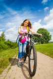 Girl with long hair holds her bike and helmet Stock Photography