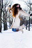 Girl with long hair jumping in the snow Stock Photos