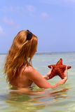 Girl with the long hair keeps starfish Royalty Free Stock Images