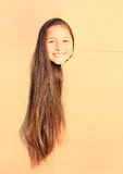 Girl with long hair looking thru hole Stock Photography