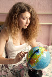 The girl with long hair looks for something on the globe Stock Photo