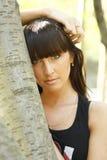 Girl with long hair near tree. Young beautiful girl with long hair stands on open-air near tree Stock Photo