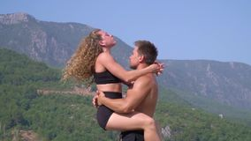 Gymnasts on vacation in Turkey. A girl with long hair performs a complicated trick with her partner, slow motion stock footage