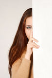 A girl with long hair. The picture shows a beautiful girl with long brown hair. Half of her face is hidden behind a wall Royalty Free Stock Photos