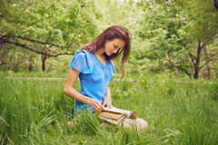 Girl with long hair reads a book in park Royalty Free Stock Image