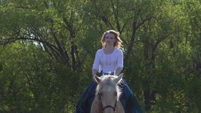 A girl with long hair, riding a horse in a long green and blue historical dress, looking at the camera, the horse is stock video