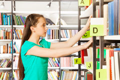 Girl with long hair searches book in library Stock Photography