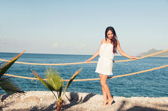 Girl with long hair in a short white dress on the pier Royalty Free Stock Photos