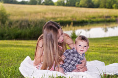 Girl with long hair sitting on a blanket with curious baby boy Royalty Free Stock Photos