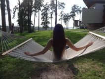 The girl with long hair. Girl sitting on a hammock. the girl at the resort Stock Photo
