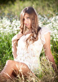 girl with long hair sitting on meadow with white flowers Royalty Free Stock Photo