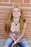 The girl with long hair sitting near wall Royalty Free Stock Photography