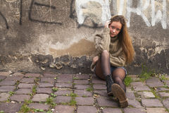Girl with long hair sitting near the wall in the old town. Royalty Free Stock Images