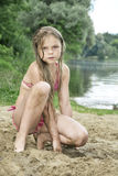 Girl with long hair sitting on the sand on the beach near the la Royalty Free Stock Image