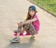 Girl with long hair sitting on skating board Stock Photos