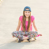 Girl with long hair sitting on skating board Stock Images