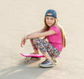 Girl with long hair sitting on skating board Stock Photography