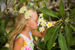 Girl with long hair smelling the flowers on the tree Stock Photo