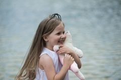 Girl with long hair smile with soft toy stock photography