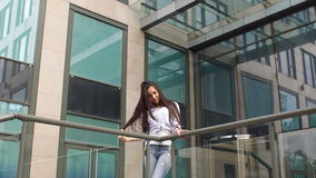 Girl with long hair standing near modern building. stock footage