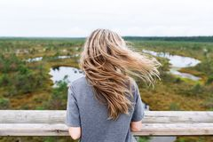 The girl with long hair stopped on bridge with backpack to enjoy nature. The girl with beautiful long hair stopped on bridge with backpack to enjoy nature in stock photos
