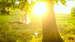 Girl with long hair swinging on swing in sun on a tree in park stock footage