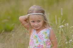 Girl with long hair walking along the field on a warm summer day Stock Photography
