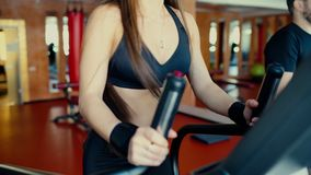 The girl with long hair walking, running on treadmill gym workout 4 k. Woman with long hair, peoples walking, running on treadmill gym workout, mirrored stock footage
