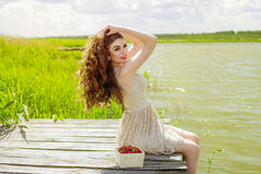 Girl with long hair in water in summer with strawberries Stock Photography